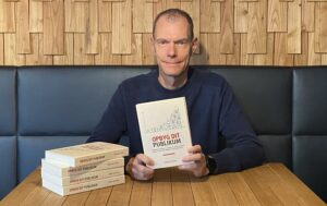 René Hjetting sidder med bogen: Opbyg dit publikum